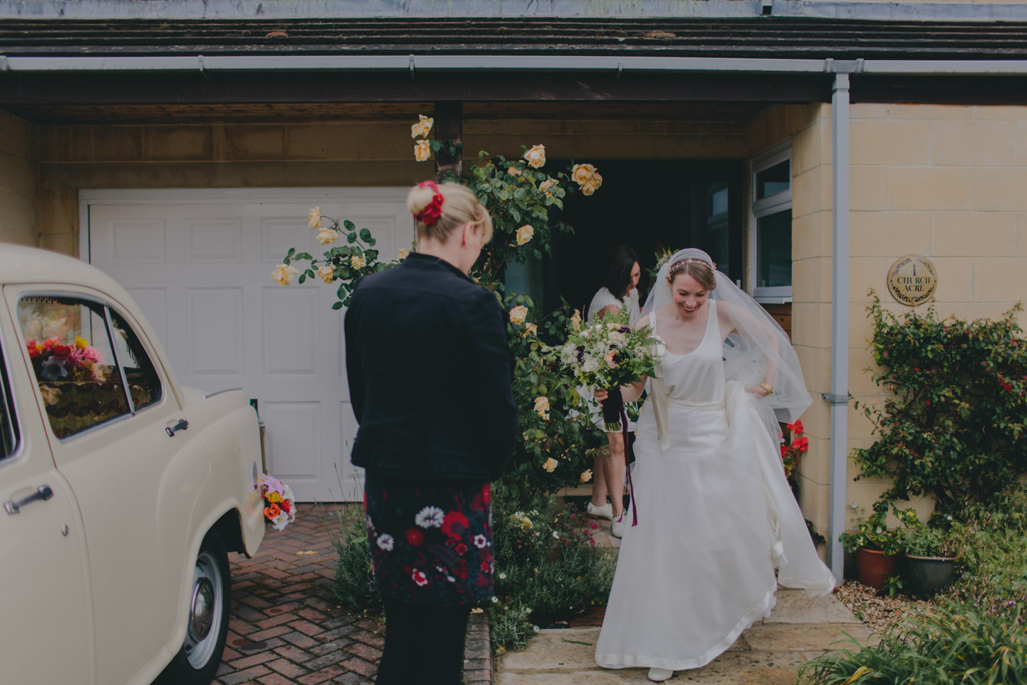 Bride and father leaving family home on wedding day