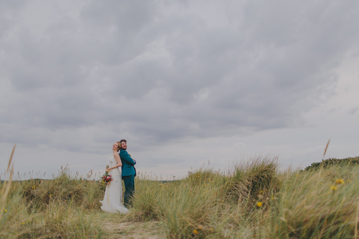photograph of bride and groom having fun in Norfolk  Dunes