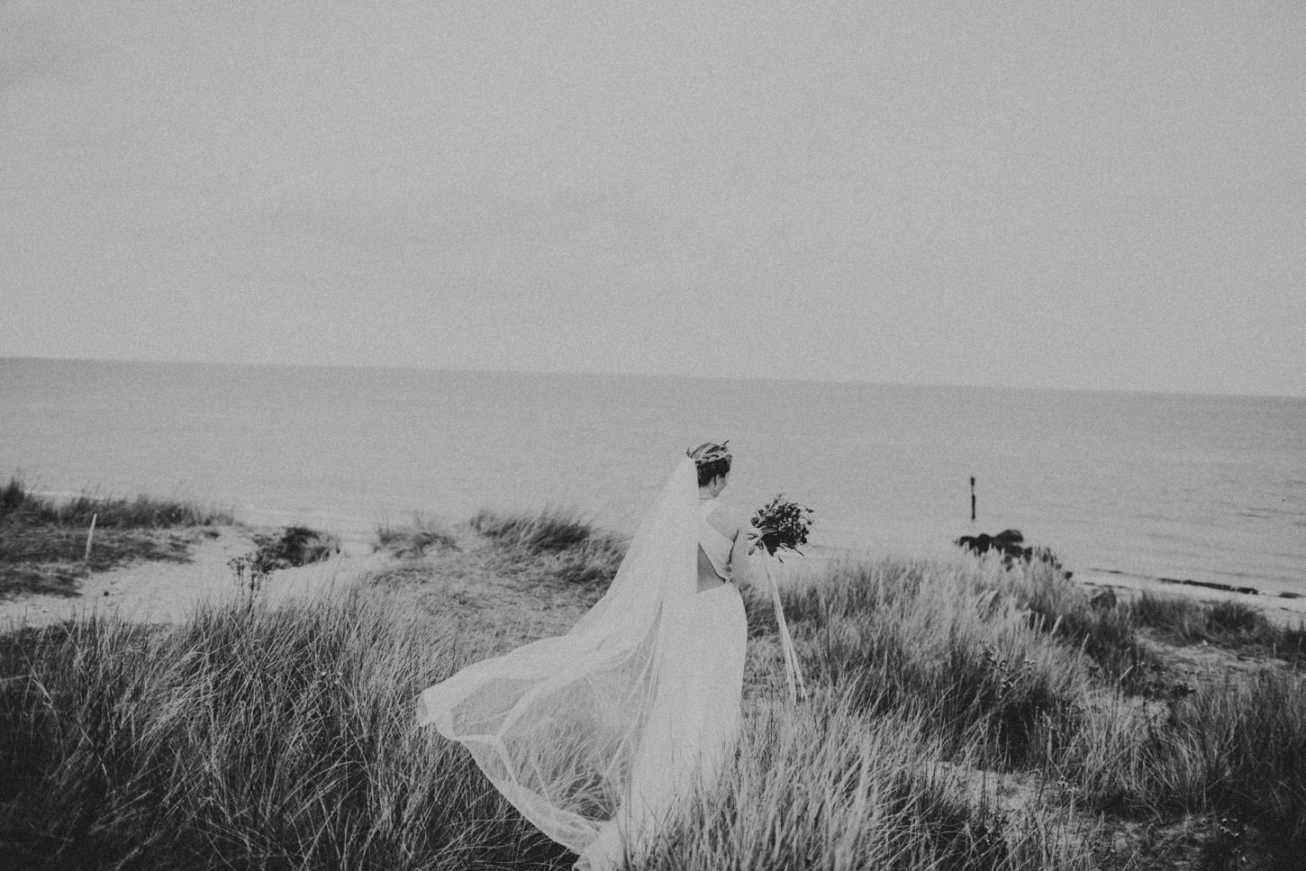 black and white image of bride in dunes