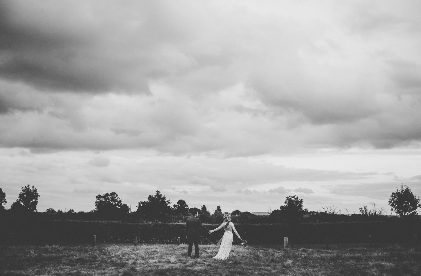 bride and groom in field by Tori Hancock Photography